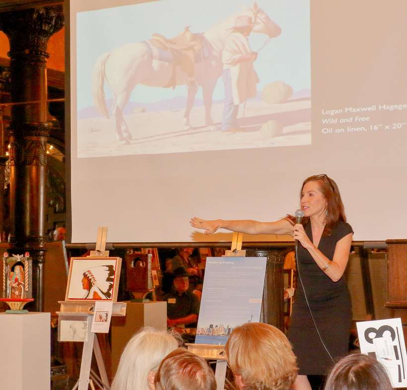 "Auctioneer Alissa Ford fires up the crowd for Logan Maxwell Hagege's ""Wild and Free,"" which was the night's co-top gainer at $12,000."