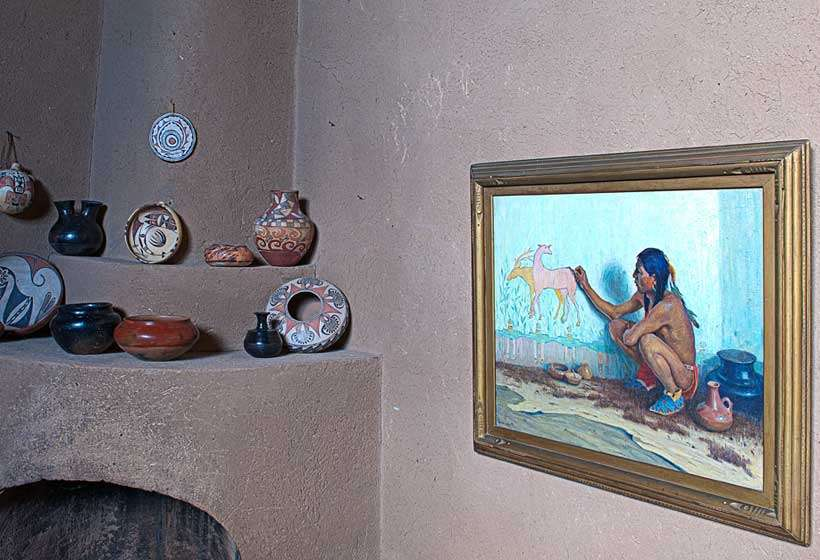 "Corner fireplace with his painting ""Indian Artist."""