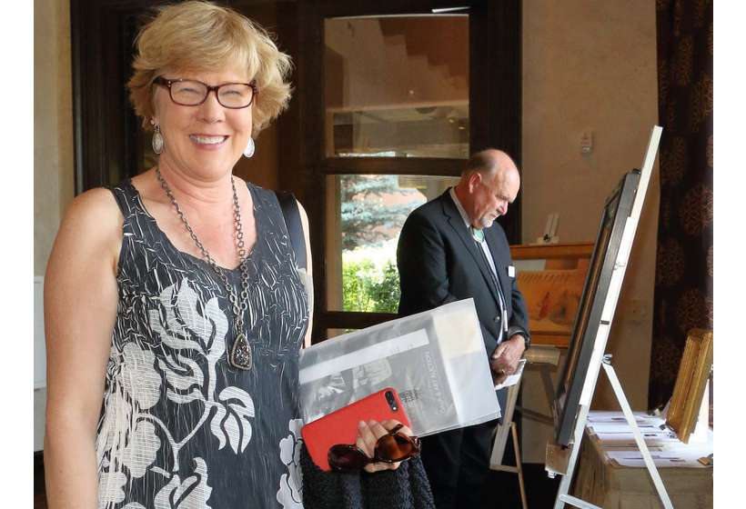 Patron Hallie Marcotte, with Board Chairman and Vice President Rich Rinehart in background, peruses the 2017 silent auction. Rich is now president of the Foundation.