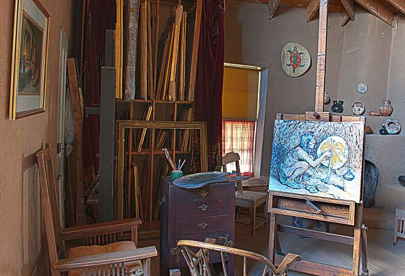 Corner of Couse studio with incomplete painting, brushes, easel, and frames.